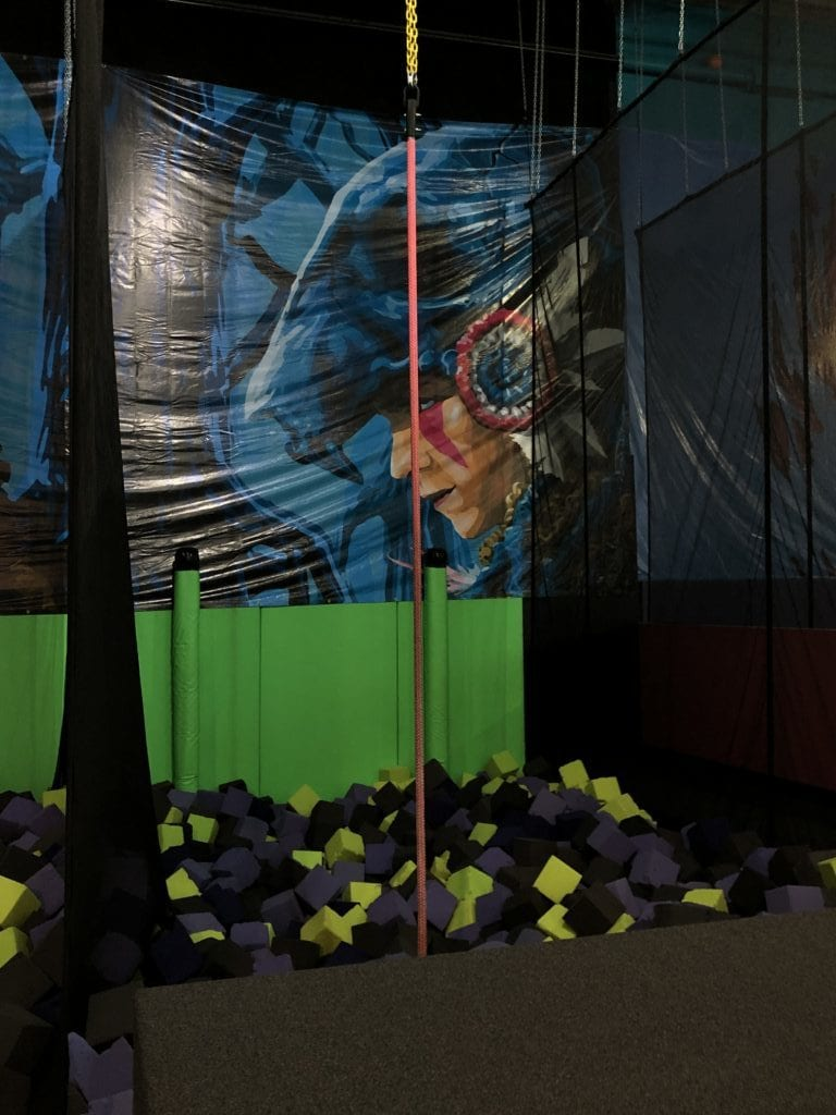 swinging rope over foam pit at flying squirrel indoor trampoline fun park